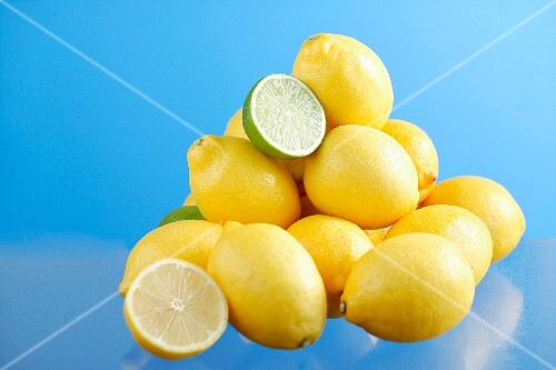 Lemons and limes on a blue surface