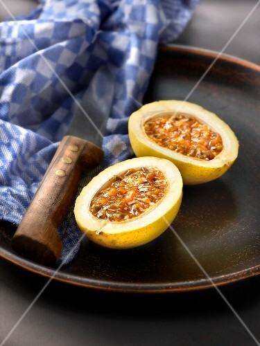 A passion fruit, halved, on a plate with a knife and a tea towel