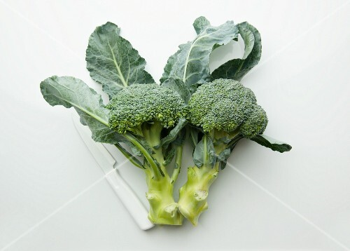 Broccoli with a knife on a white surface