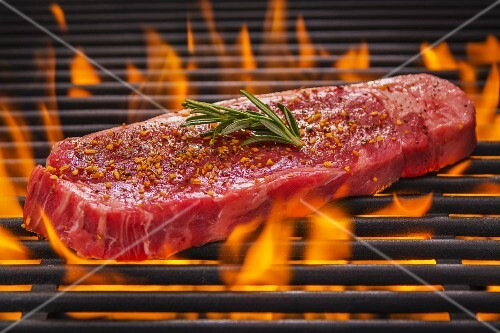 Tri tip steak with rosemary and spices on a flaming barbecue