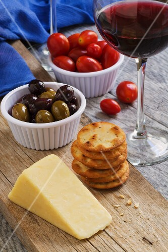 Cheddar cheese, crackers, Kalamata olives, tomatoes and a glass of red wine on a rustic wooden table