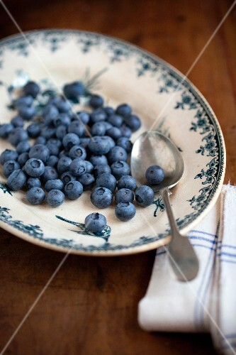 Blueberries with a spoon on a vintage plate