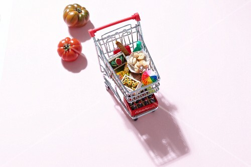 A mini shopping trolley filled with toy foodstuffs next to fresh tomatoes