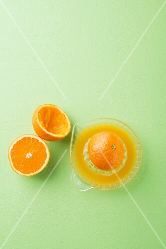 An arrangement of oranges with a juicer and freshly pressed juice