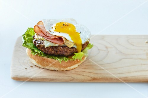 A hamburger with lettuce, ham, cheese and a fried egg