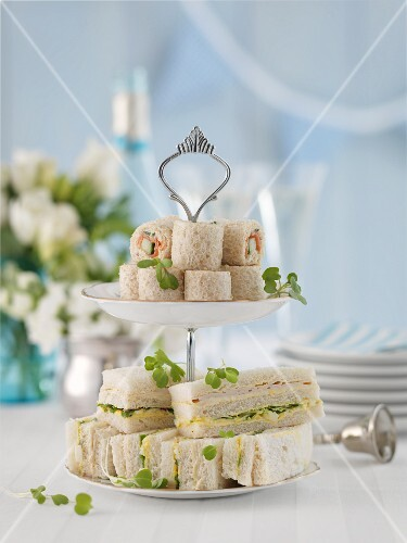 Bread wraps and sandwiches on a cake stand