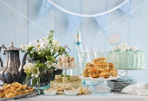 A festive buffet with a large cake and a bottle of champagne