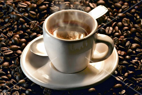 A steaming cup of espresso on roasted coffee beans