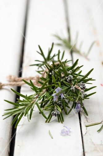 Flowering rosemary sprigs on a wooden surface