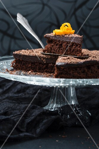 A sliced chocolate orange cake with ganache on a cake stand