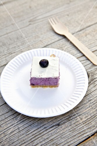 A slice of blueberry cheesecake on a paper plate