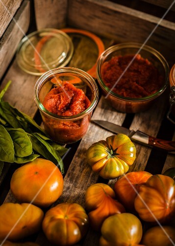 Fresh tomatoes and jars of homemade tomato purée