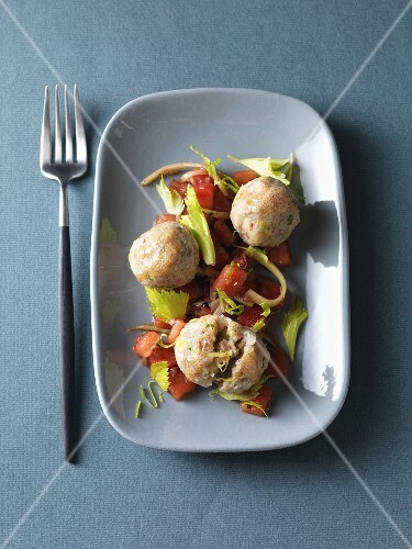 Vegetarian buckwheat dumplings on a warm tomato salad