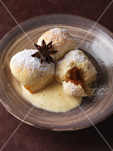 Buchteln (baked, sweet yeast dumplings) filled with preserved pears in a star anise and vanilla sauce