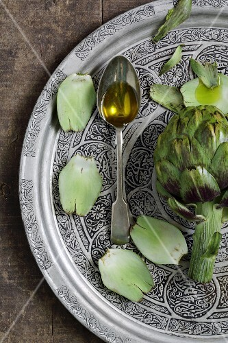 Olive oil on a spoon with artichokes
