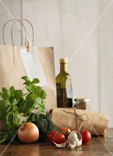 A shopping bag with vegetables and herbs