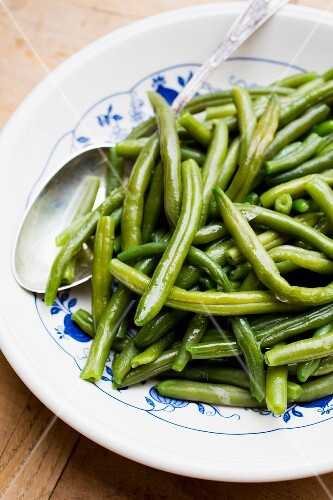 Cooked runner beans on a plate with a spoon