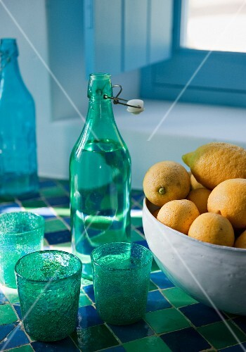 Bottles, drinking glasses and a bowl of lemons on a blue-green mosaic window sill