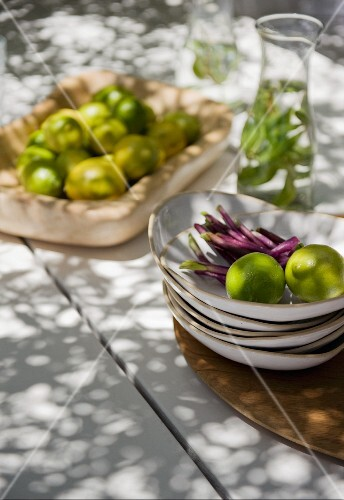 Limes in a bowl and on a stack of plates outside on a summer table