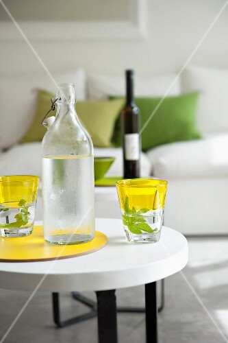 Flip-top bottles with water and drinking glasses on a round side table in a living room