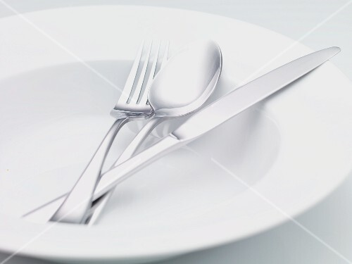 Silver cutlery on a soup plate