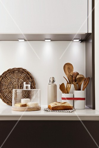 Cheese under glass cover, bread, wicker mat, stoneware bottle and kitchen utensils in wooden containers on kitchen worksurface