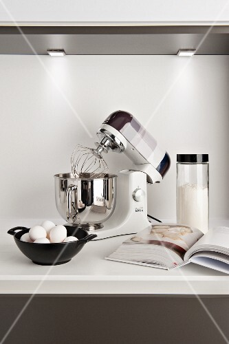 Modern mixer, eggs, flour and cookery book on kitchen worksurface