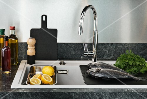 Fresh fish, oil and lemons on sink in kitchen