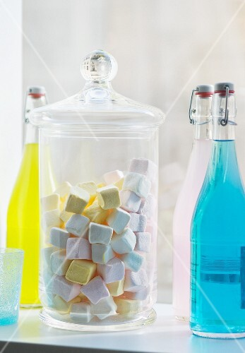 Marshmallows in a jar with colourful bottles of drink in a kitchen