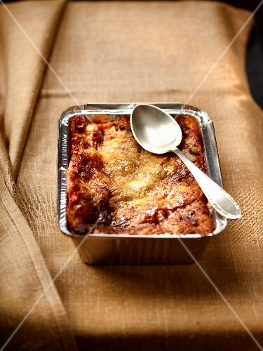 Lasagne with tomatoes and cheese in an aluminium tray with a spoon