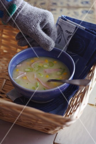 Potato soup with ham and sweetcorn in a bowl on a cork tray