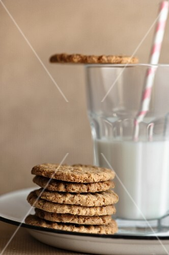 A stack of biscuits next to glass of milk