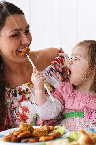 A woman and a little girl eating with chopsticks