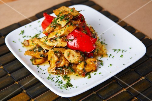 Grilled octopus in curry sauce with roasted peppers