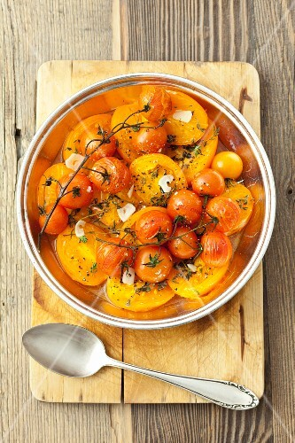 Baked yellow tomatoes and cherry tomatoes with thyme, garlic and olive oil