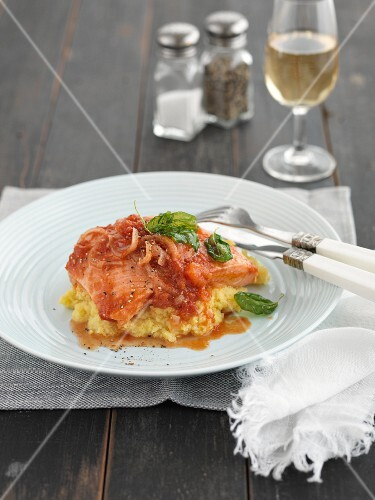 Steamed salmon with tomato sauce and fried basil on polenta