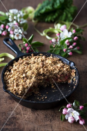 Pan-baked rhubarb pie on a wooden surface with spring flowers