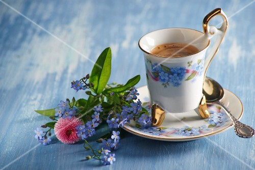 A coffee cup and a small bouquet of forget-me-not and daisies