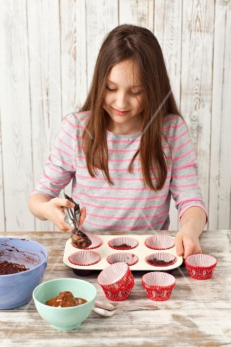 A girl preparing chocolate cupcakes - spooning the mixture into muffin cases