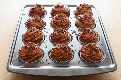 Chocolate cupcakes with butter cream and chocolate curls in a baking tin