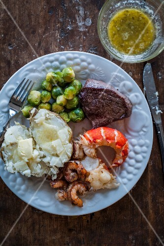Surf and turf with a baked potato and Brussels sprouts (USA)