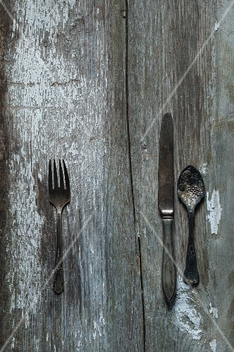 Antique cutlery and utensils on a wooden surface
