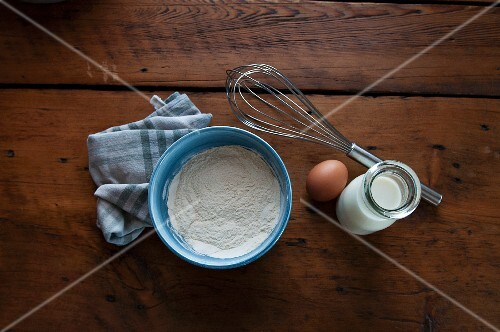 Various baking utensils (flour, egg, milk), a tea towel and a whisk