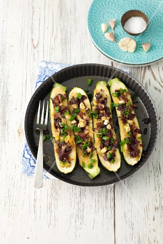 Baked courgettes stuffed with raisins, shallots and red onions