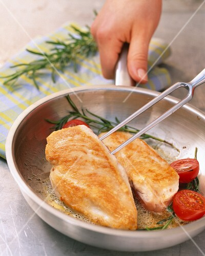 Chicken breast with tomatoes and rosemary in a pan
