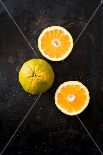 Ugli fruit, whole and halved, on a black surface