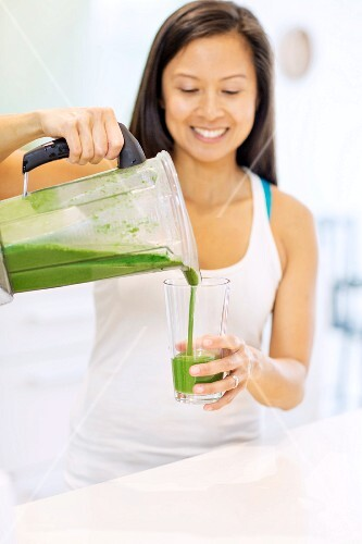 A woman pouring a smoothie into a glass