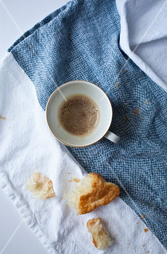 An almost empty cup of espresso and croissant crumbs on a linen cloth