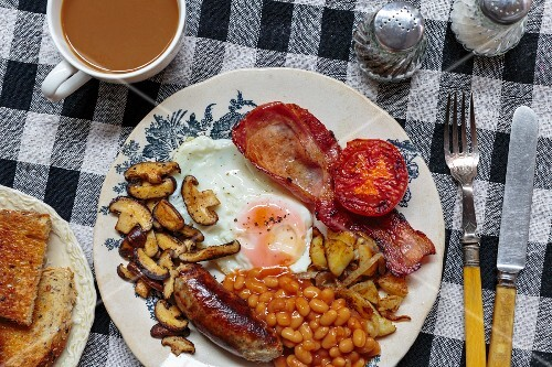 English breakfast with egg, baked beans, sausage, bacon and mushrooms (England)