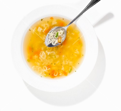 Alphabet soup in a bowl with a spoon